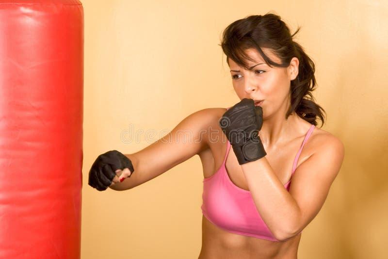 Entrenamiento de Kickboxing, mujer en el retroceso del bolso de perforación con el pie foto de archivo