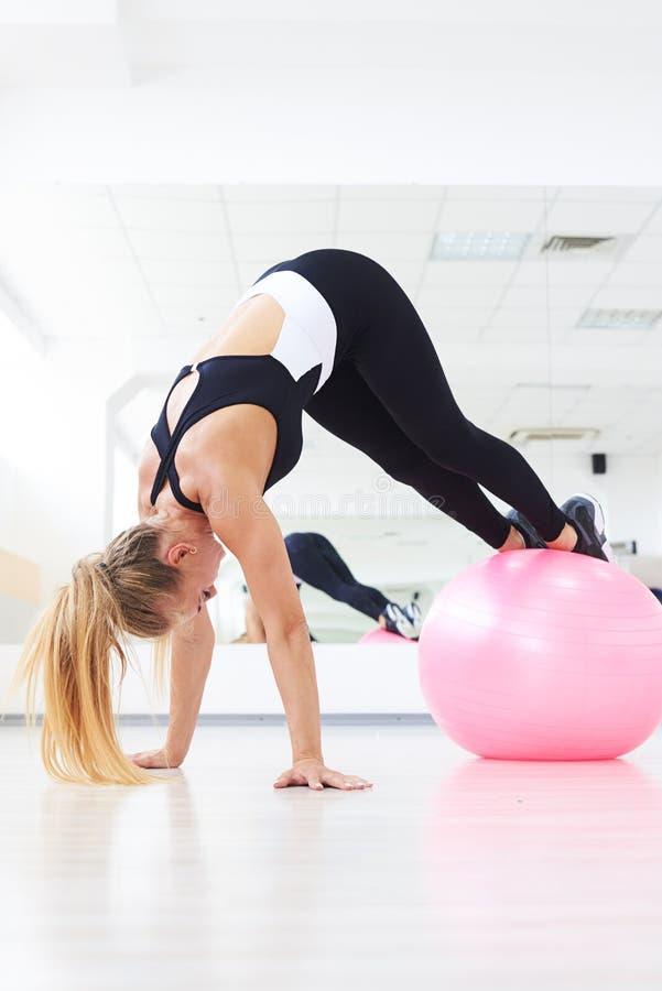 Entrenamiento de la aptitud de la mujer bastante joven en gimnasio con el fitball foto de archivo libre de regalías