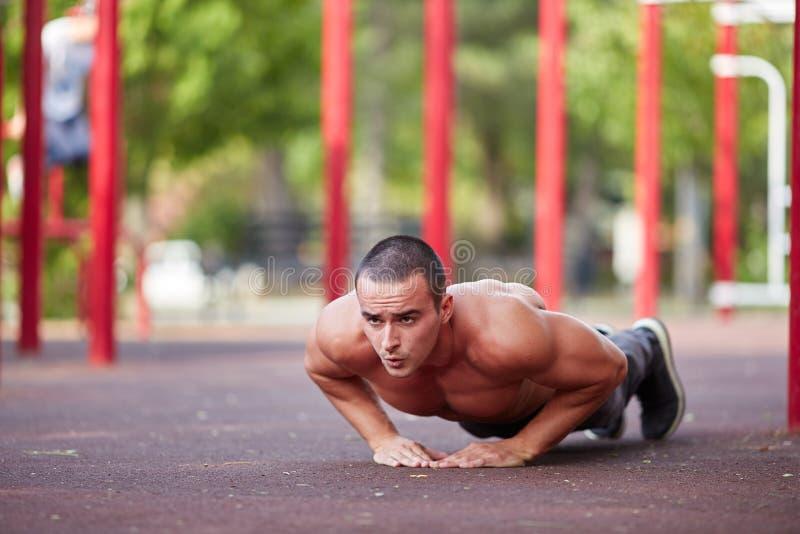 Entrenamiento de la calle - entrenamiento muscular hermoso del hombre en el parque fotografía de archivo