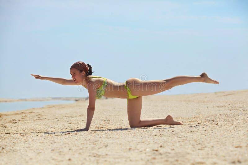 Entrenamiento de la chica joven en la playa imagenes de archivo