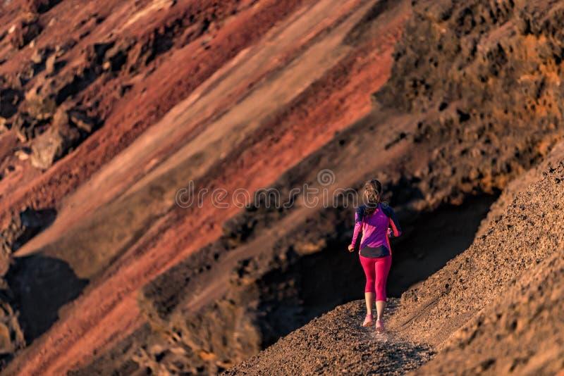 Entrenamiento de la muchacha del corredor que corre en rastro del lado de la montaña del volcán Mujer joven en ultra el atleta de foto de archivo libre de regalías
