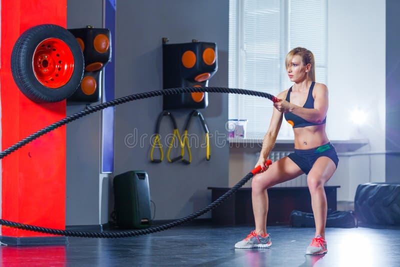 Entrenamiento de la mujer con la cuerda de la batalla en gimnasio apto de la cruz fotografía de archivo