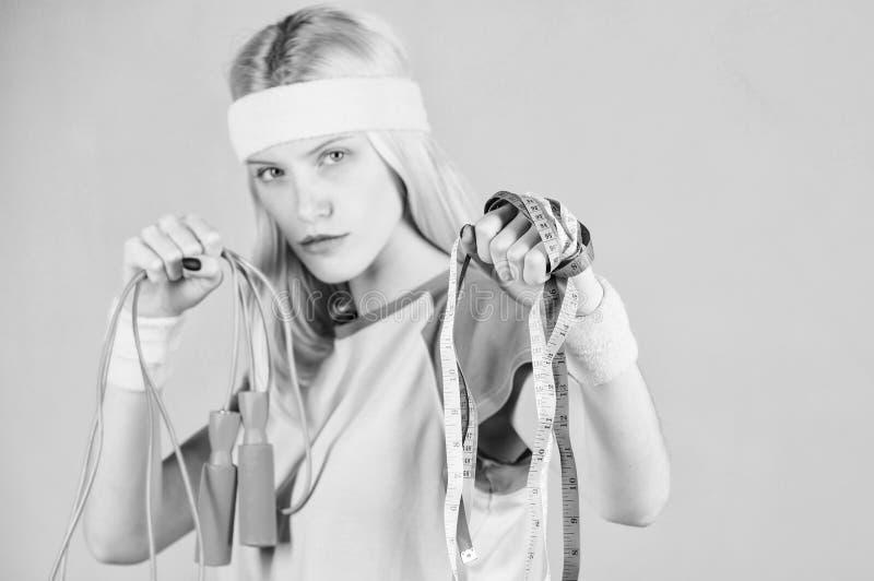 Entrenamiento de la mujer con la cuerda de salto Resultado del entrenamiento Cinta de la cuerda y de la medida de salto del contr imágenes de archivo libres de regalías