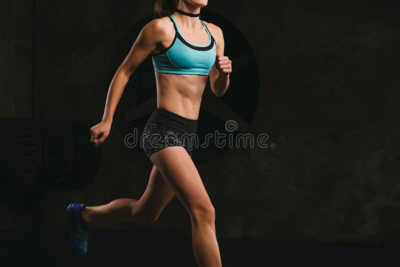 Entrenamiento de la mujer de la aptitud del deporte en fondo oscuro Carrocería hermosa fotografía de archivo