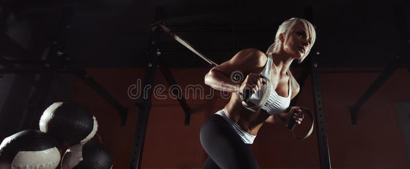 Entrenamiento de la mujer de la aptitud en el TRX en el gimnasio fotografía de archivo