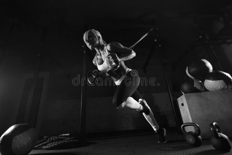 Entrenamiento de la mujer de la aptitud en el TRX en el gimnasio fotografía de archivo libre de regalías