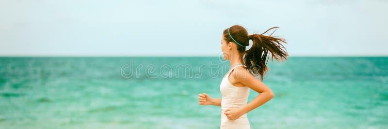 Entrenamiento de la mujer del ajuste en el entrenamiento cardiio al aire libre que corre en fondo azul del océano de la playa imagenes de archivo