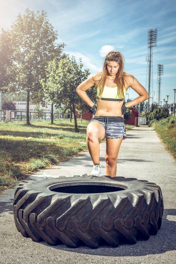 Entrenamiento de la mujer del deporte con el neumático foto de archivo