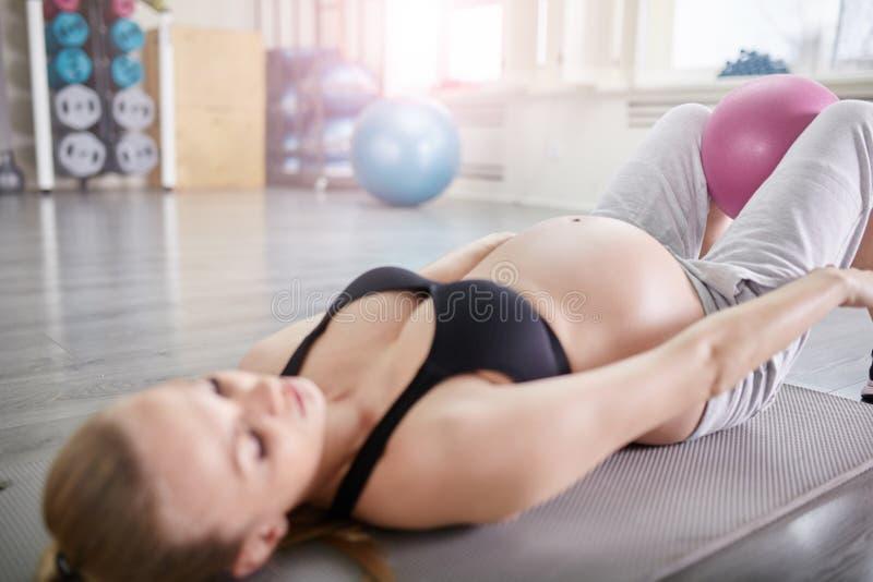 Entrenamiento de la mujer embarazada con la bola de los pilates entre las piernas fotografía de archivo