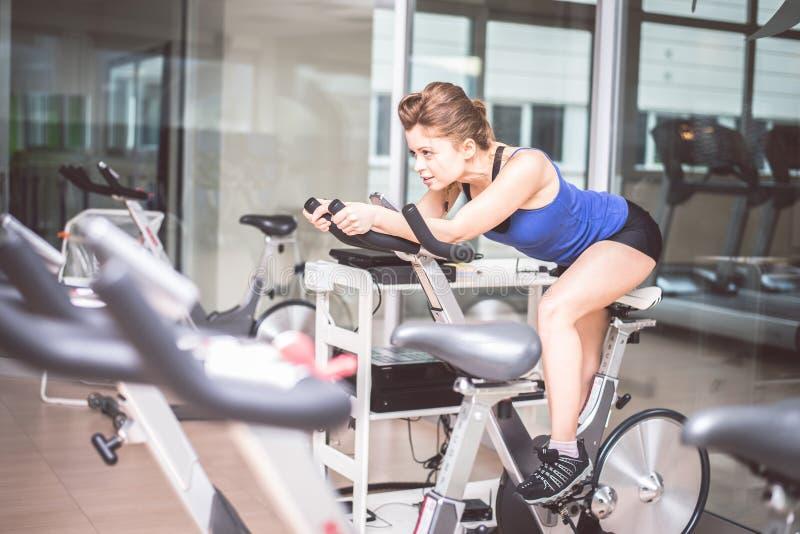 Entrenamiento de la mujer en la bici en un gimnasio foto de archivo libre de regalías