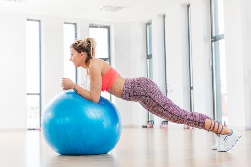 Entrenamiento de la mujer joven con el fitball en el club de fitness foto de archivo libre de regalías