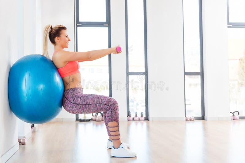 Entrenamiento de la mujer joven con el fitball en el club de fitness imagenes de archivo