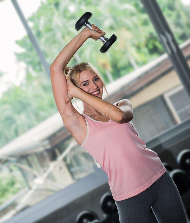 Entrenamiento de la mujer joven con pesa de gimnasia fotografía de archivo libre de regalías