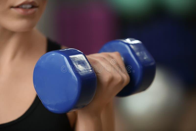 Entrenamiento de la mujer joven con pesa de gimnasia en el gimnasio moderno, primer fotos de archivo
