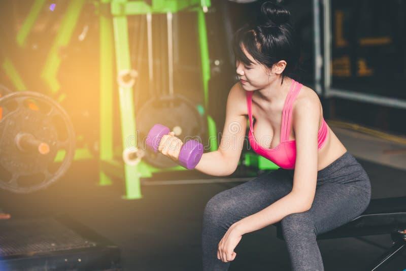 Entrenamiento de la mujer joven con pesa de gimnasia en gimnasio imágenes de archivo libres de regalías