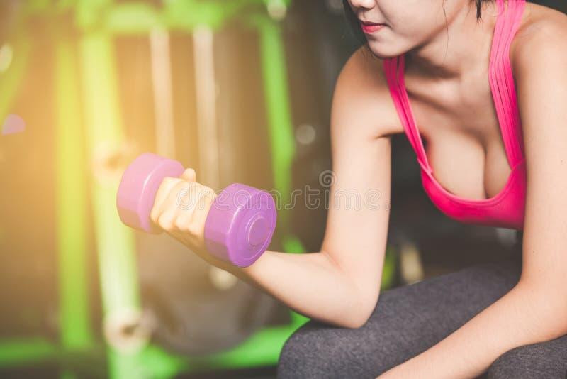 Entrenamiento de la mujer joven con pesa de gimnasia en gimnasio fotos de archivo
