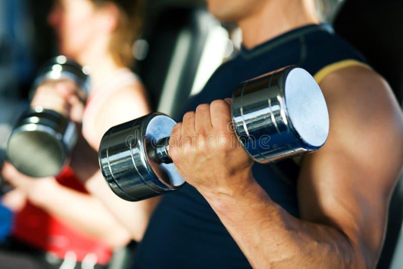 Entrenamiento de la pesa de gimnasia en gimnasia imágenes de archivo libres de regalías