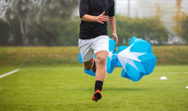 Entrenamiento de la resistencia del fútbol del fútbol Velocidad o prueba de Sprint con el paracaídas Prueba de fuerza profesional fotos de archivo