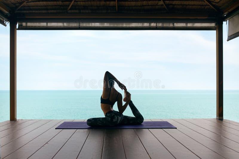 Entrenamiento de la yoga La mujer en deporte viste estirar el cuerpo cerca del mar fotografía de archivo