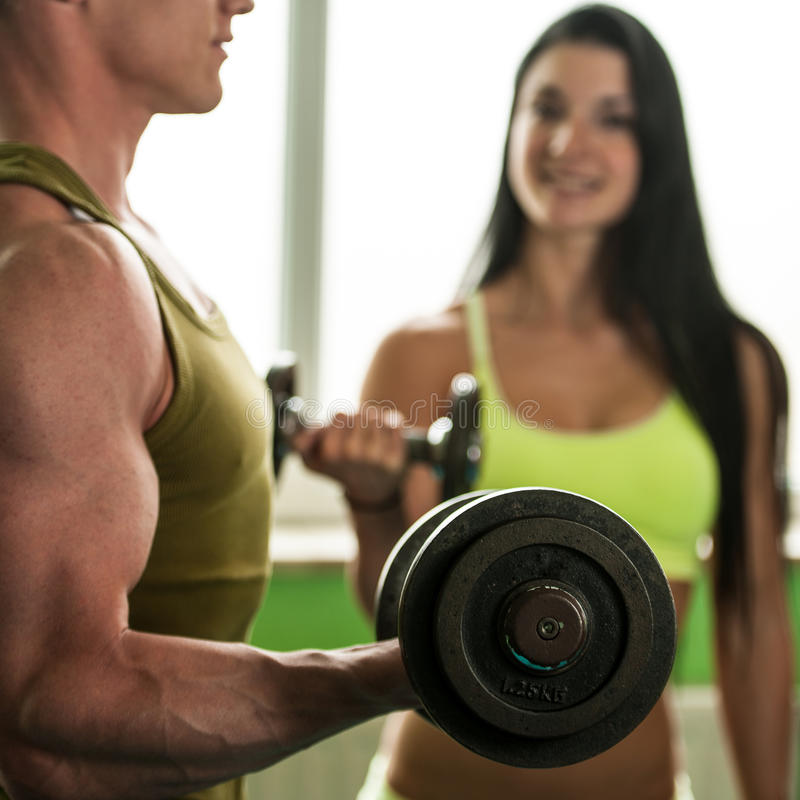 Entrenamiento de los pares de la aptitud - el hombre y la mujer aptos entrenan en gimnasio fotografía de archivo
