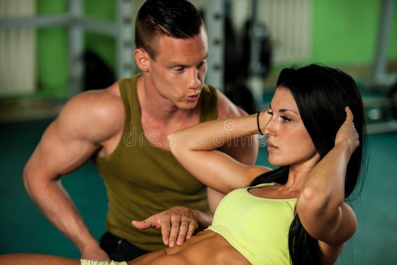 Entrenamiento de los pares de la aptitud - el hombre y la mujer aptos entrenan en gimnasio imagen de archivo libre de regalías