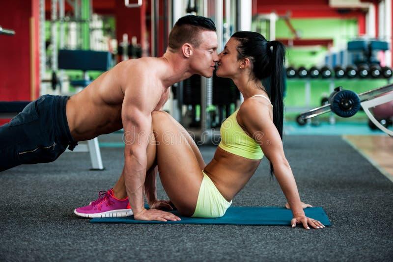 Entrenamiento de los pares de la aptitud - mann y la mujer aptos entrenan en gimnasio foto de archivo libre de regalías
