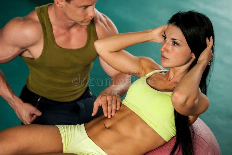 Entrenamiento de los pares de la aptitud - mann y la mujer aptos entrenan en gimnasio imagenes de archivo