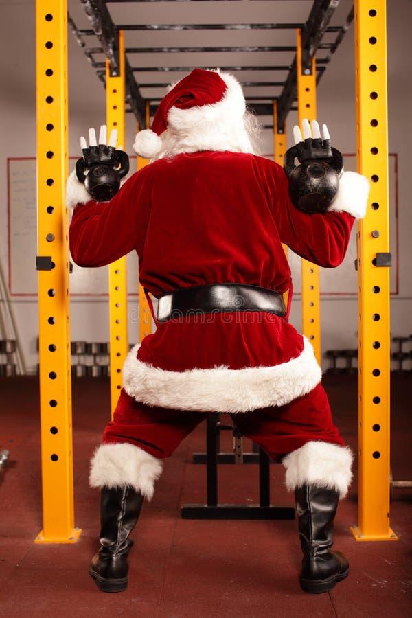 Entrenamiento de Santa Claus antes de la Navidad en gimnasio - visión trasera imagen de archivo