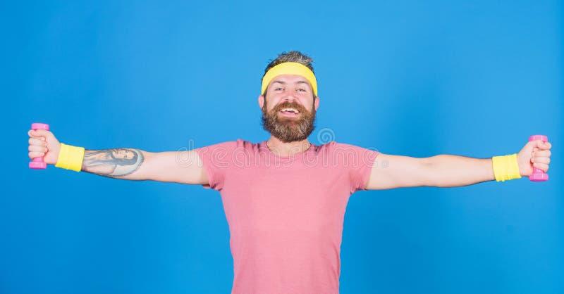 Entrenamiento del atleta con poca pesa de gimnasia Atleta barbudo del hombre que ejercita pesa de gimnasia Individuo motivado del fotografía de archivo libre de regalías