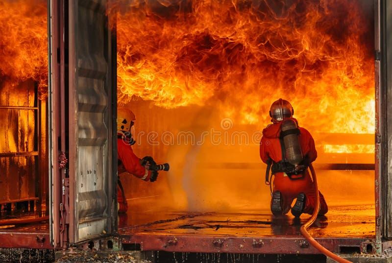 Entrenamiento del bombero con el gas y la llama foto de archivo