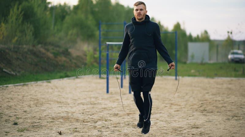 Entrenamiento del boxeador del retroceso del hombre joven con la cuerda que salta en parque de la ciudad fotografía de archivo