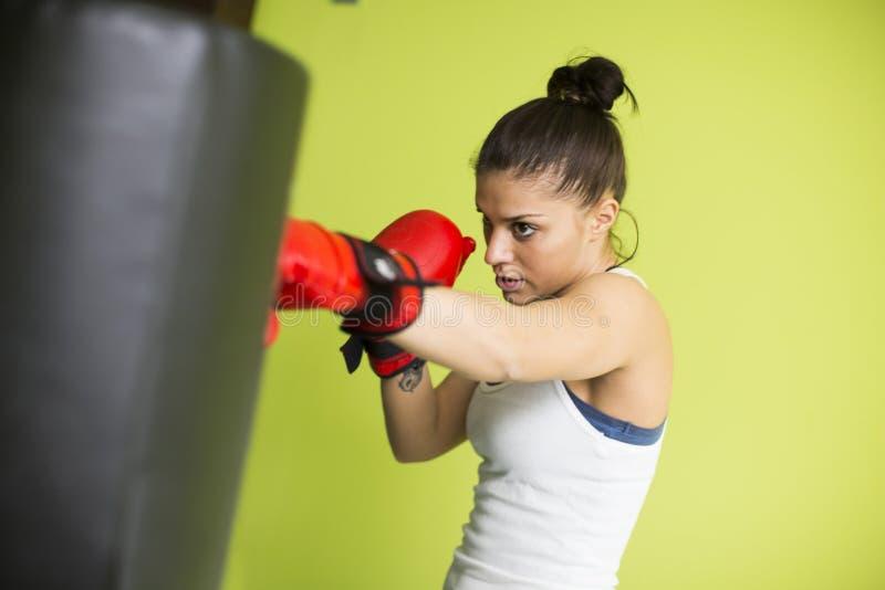 Entrenamiento del boxeo de la mujer adentro en un nuevo gimnasio ligero foto de archivo libre de regalías
