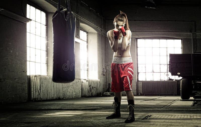 Entrenamiento del boxeo de la mujer joven en un edificio viejo foto de archivo