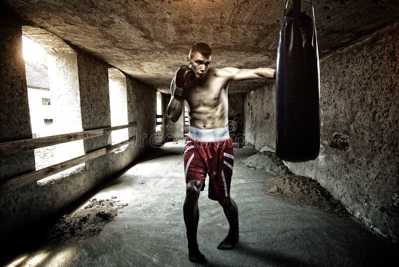 Entrenamiento del boxeo del hombre joven en un edificio viejo foto de archivo libre de regalías