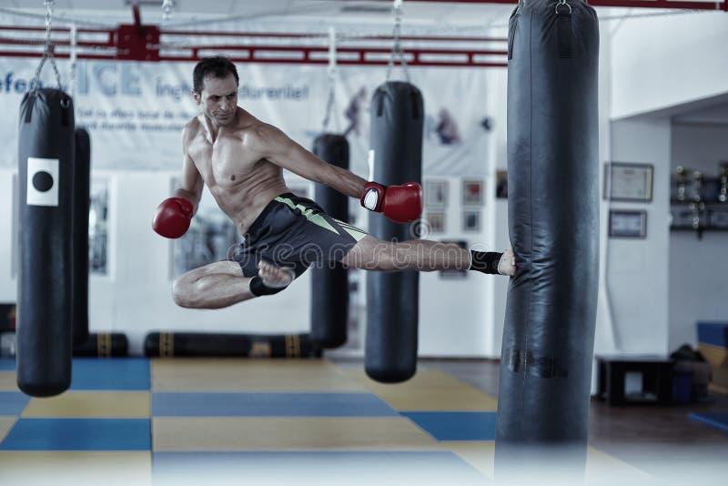 Entrenamiento del combatiente de Kickbox con el bolso de sacador imagen de archivo libre de regalías