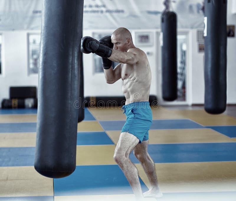 Entrenamiento del combatiente de Kickbox con el bolso de sacador fotos de archivo libres de regalías