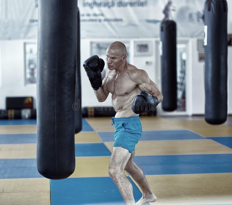 Entrenamiento del combatiente de Kickbox con el bolso de sacador imagen de archivo