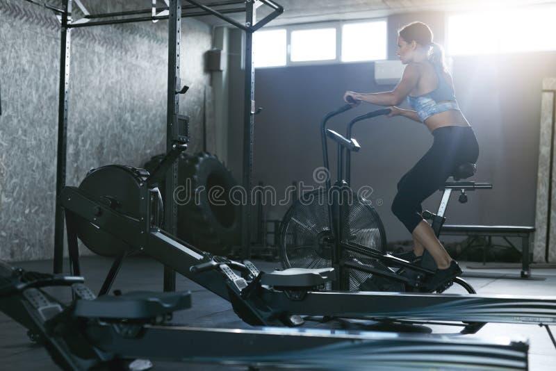 Entrenamiento del deporte en el gimnasio Entrenamiento de la mujer en la bicicleta de Crossfit imagen de archivo libre de regalías