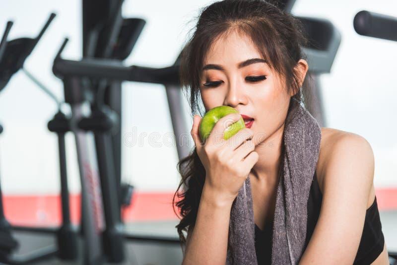 Entrenamiento del ejercicio de la mujer en la aptitud del gimnasio que sostiene la fruta verde de la manzana fotos de archivo libres de regalías