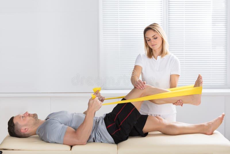 Entrenamiento del hombre con la banda del ejercicio ayudada por el fisioterapeuta fotografía de archivo