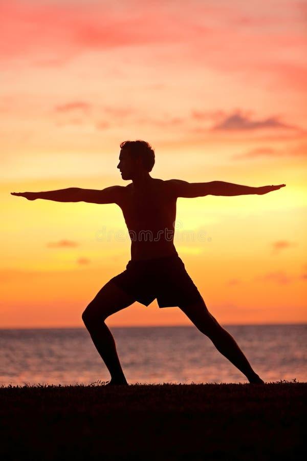 Entrenamiento del hombre de la yoga y el meditar en actitud del guerrero imágenes de archivo libres de regalías