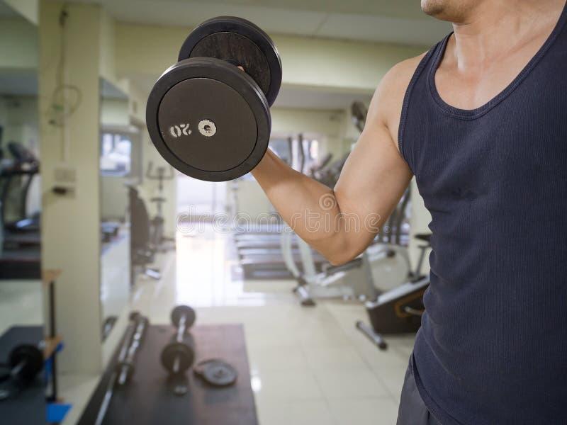 Entrenamiento del hombre en el gimnasio - los bíceps de la pesa de gimnasia se encrespan fotografía de archivo libre de regalías