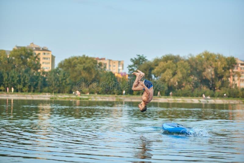 Entrenamiento del hombre en el tablero de paleta, saltando en la cabeza del agua abajo en el lago de la ciudad foto de archivo