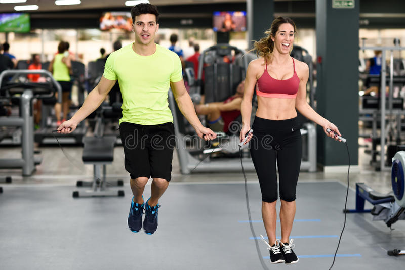 Entrenamiento del hombre y de la mujer con la cuerda de salto en gimnasio del crossfit foto de archivo