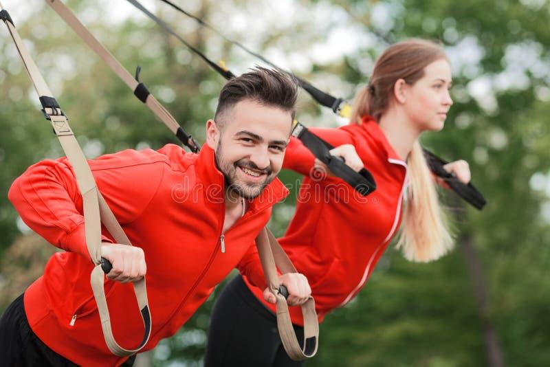 Entrenamiento del hombre y de la mujer del deporte en parque imagen de archivo