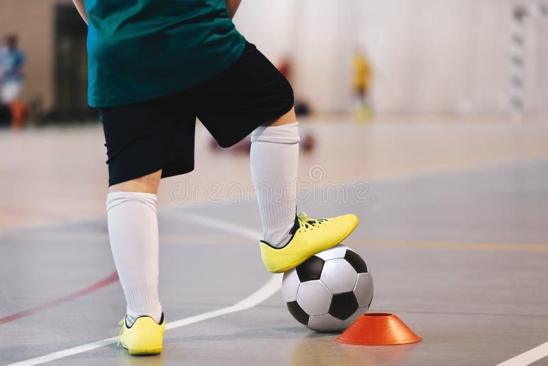 Entrenamiento del jugador de fútbol sala con las bolas Pasillo de deportes del fútbol sala Jugador futsal del fútbol, bola, piso  imagen de archivo libre de regalías