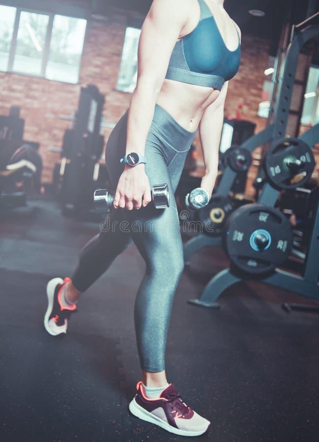 Entrenamiento del músculo de la pierna, estocadas con pesas de gimnasia Mujer modelo atlética con el cuerpo de deportes que ejerc fotos de archivo