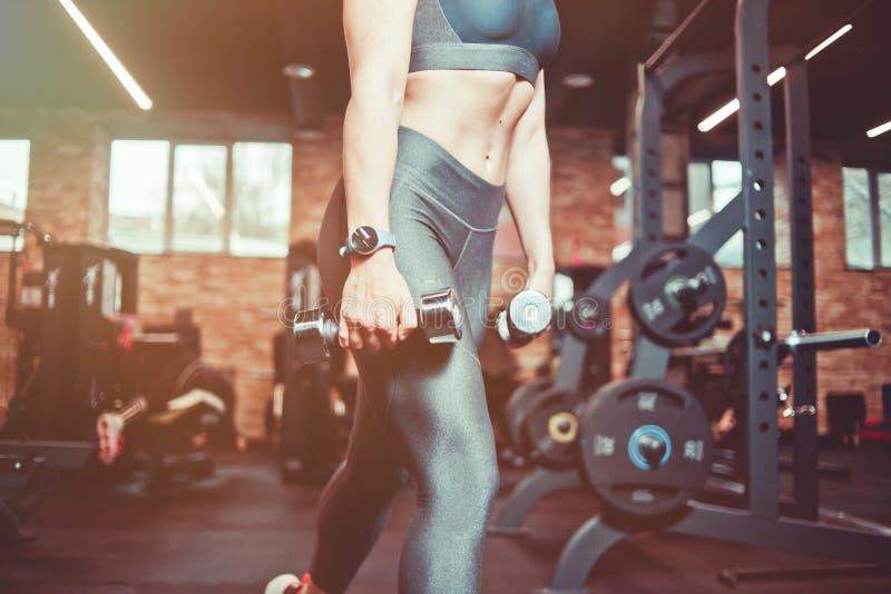 Entrenamiento del m?sculo de la pierna, estocadas con pesas de gimnasia Mujer modelo atl?tica con el cuerpo de deportes que ejerc imagen de archivo libre de regalías