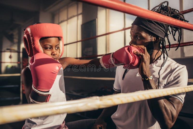 Entrenamiento del niño del boxeo con su coche en un gimnasio del boxeo fotografía de archivo libre de regalías