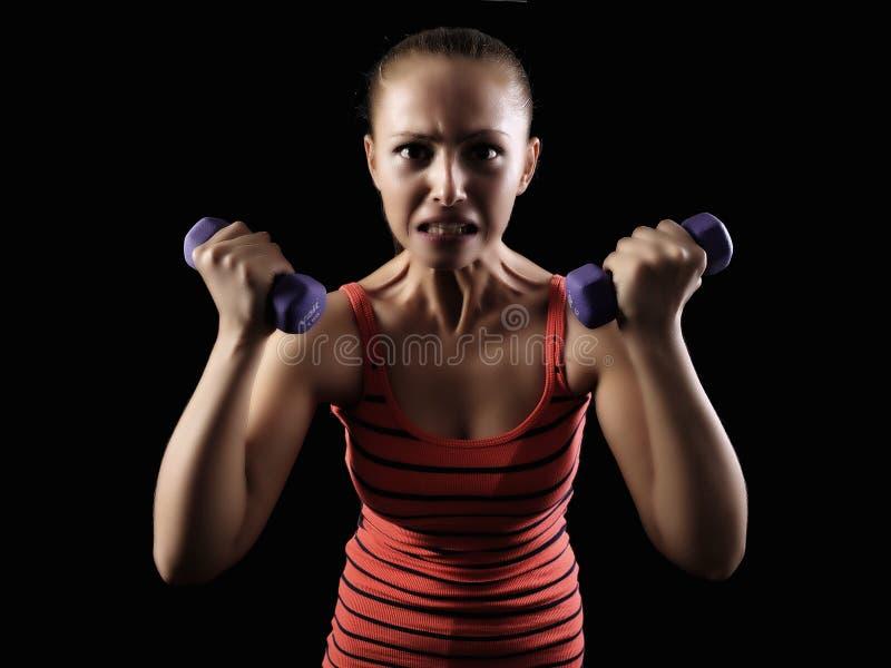 Entrenamiento del peso de la mujer de la pesa de gimnasia en gimnasia foto de archivo